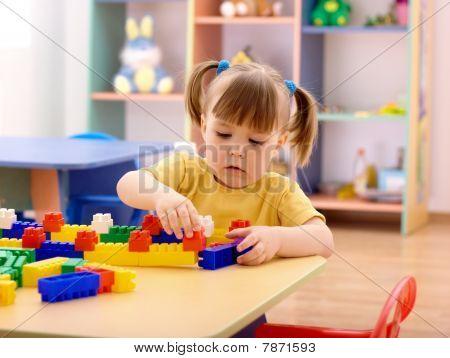 Little Girl Play With Building Bricks In Preschool