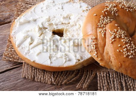Bagel With Cream Cheese And Sesame Close-up On A Wooden Table