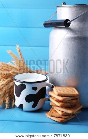 Retro can for milk, milk in cup, cookie and sheaf on color wooden background