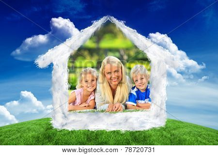 Mother with her children lying down during the summer against green field under blue sky