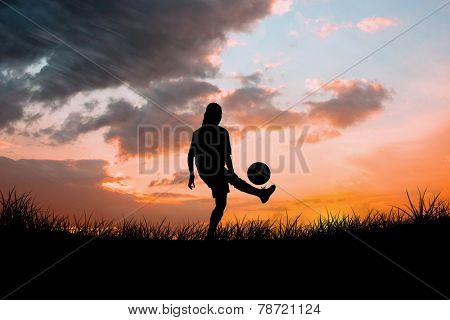 Cute football player kicking ball against sun set