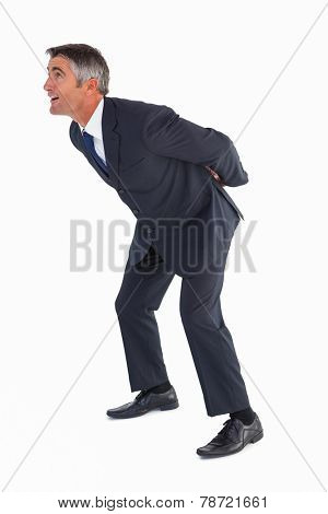 Businessman bending with arms on his back on white background
