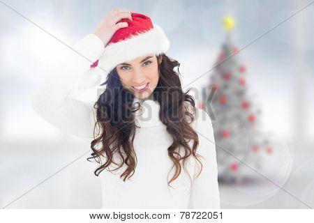 Confused brunette in santa hat against blurry christmas tree in room