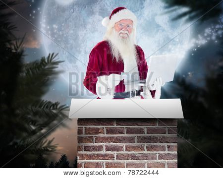 Santa pays with credit card on a laptop against full moon over forest