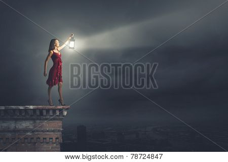 Young attractive woman in red dress with lantern