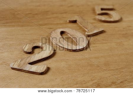 wooden numbers forming 2015, as the new year, on a wooden surface