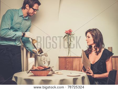 Waiter offering wine to lady in restaurant