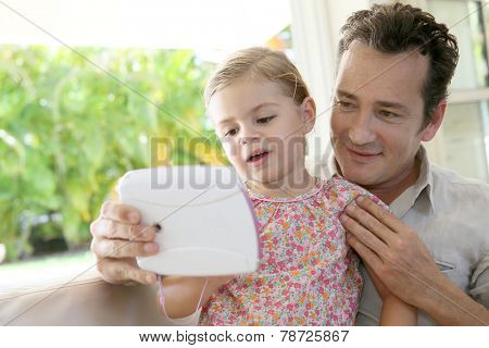 Man with daughter playing with child's tablet