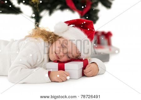 Festive little girl napping on a gift against snow