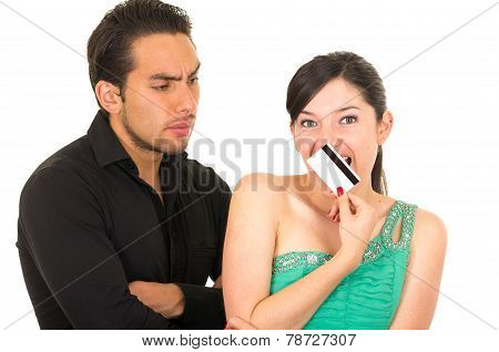 worried man looking at shopaholic wife holding credit card