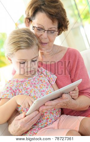 4-year-old girl with grandma playing on digital tablet
