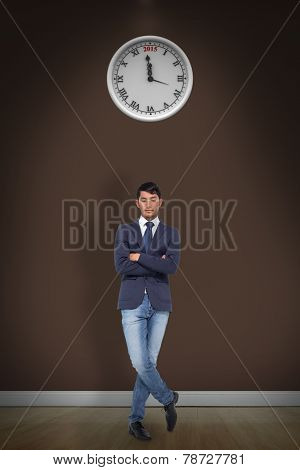 Unsmiling casual businessman with arms crossed against room with wooden floor