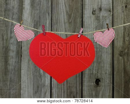 Red heart sign and striped fabric hearts hanging on clothlesline by shabby wooden background