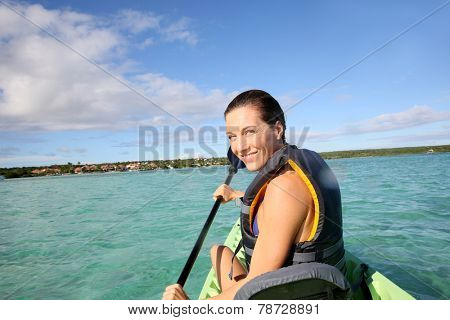 Woman paddling in canoe on blue lagoon