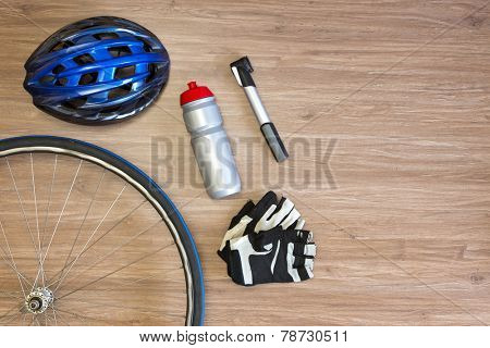 Cycling sports items arranged on a wooden background, seen from above. Items include a sports helmet, spoked wheel, drinking bottle, lightweight air pump and gloves