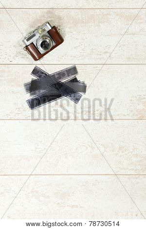 Vintage photography background with a retro rangefinder and 35 negative film strips on a white wooden surface