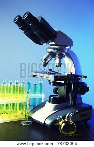 Microscope and test tubes on table, on color background