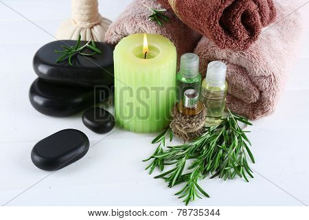 Branches of rosemary and sea salt, towels, candle and bottle with massage oil on color wooden background. Rosemary spa concept