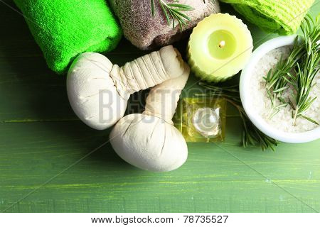 Branches of rosemary and sea salt in bowl, towels, candle and bottle with massage oil on color wooden background. Rosemary spa concept