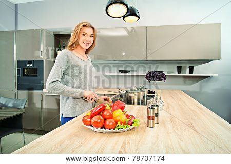 Happy young woman prepares healthy food in the kitchen. Healthy eating. Home interior.