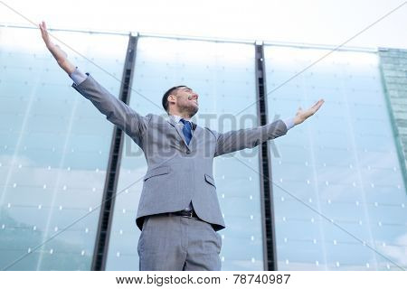 business, people and education concept - young smiling businessman with raised hands over office building