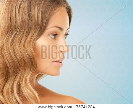 beauty, people and health concept - beautiful young woman face over blue background