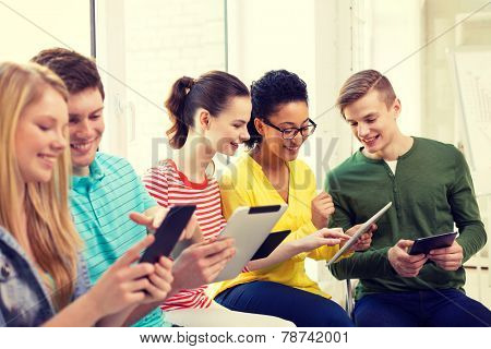 education, technology and internet concept - smiling students looking at tablet pc computer at school