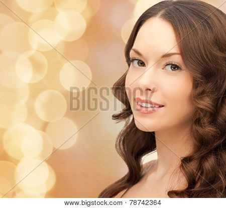 beauty, people and health concept - beautiful young woman with bare shoulders and long wavy hair over beige lights background
