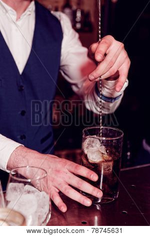 Bartender is stirring cocktail on bar counter, toned image