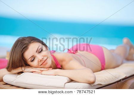 Beautiful young woman lying on a lounger by the sea.
