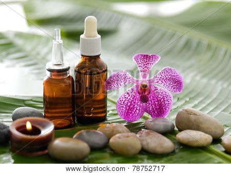 spa supplies with orchid, oil, candle , stones on banana leaf