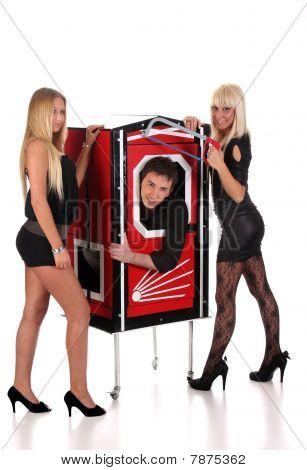 Desempenho de Mago e duas meninas de beleza em uma caixa mágica com serrote