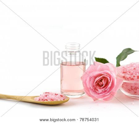 Spa setting with rose with massage oil ,salt in bowl ,spoon on white background