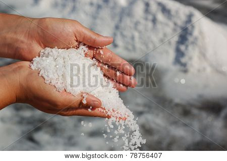 Hands Full Of Salt With Piles In The Background