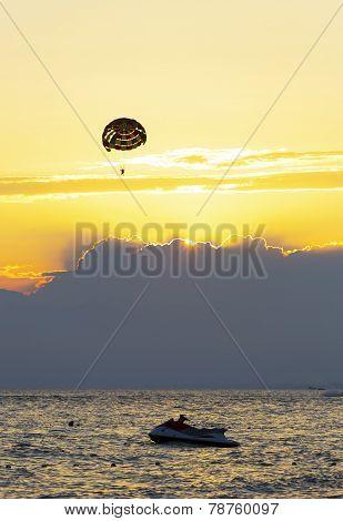Parasailing and jet ski at sunset