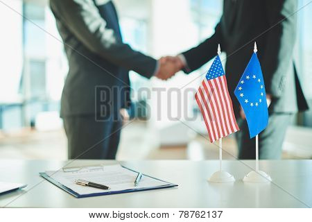 American flag, flag of European Union and contract on background of businessmen handshaking