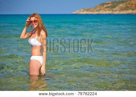 Attractive girl in bikini bathing in the sea at summer resort