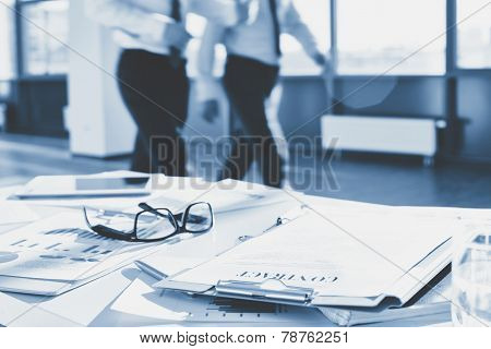 Business documents and eyeglasses on the desk in office