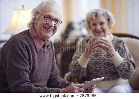 Elderly man with touchpad looking at camera with his wife on background