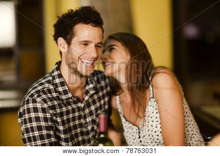 Young Woman Whispering Into Her Boyfriend's Ear