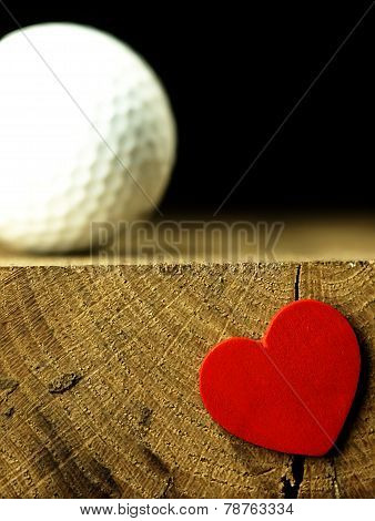 Golf Ball And Heart On The Edge Of Table.