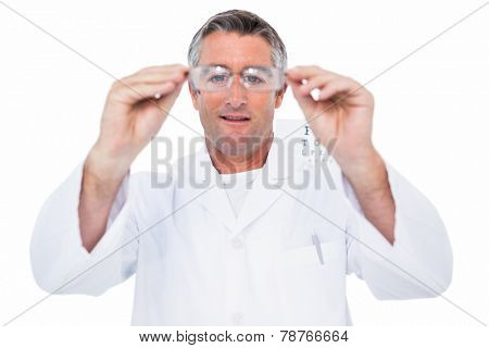 Optician in coat holding glasses on white background