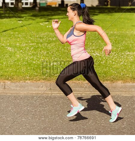 Fit brunette going faster on path in the park