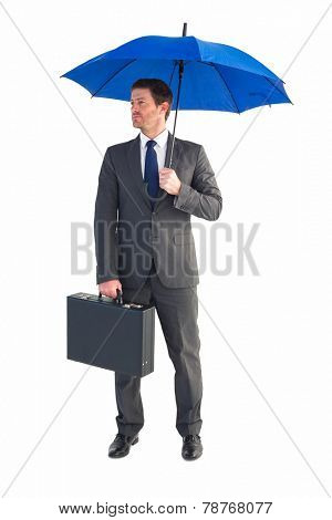 Businessman sheltering under blue umbrella on white background