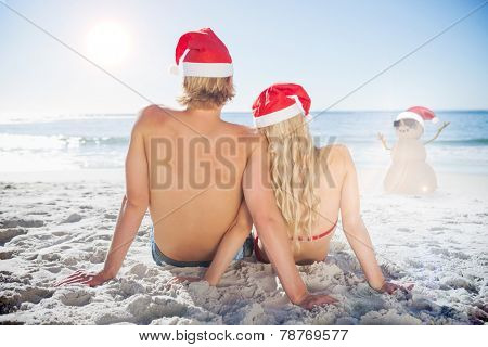 Rear view of couple sitting on beach against festive sandman