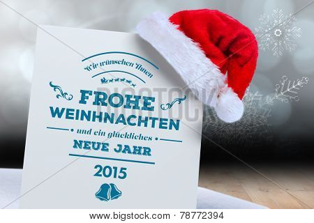 German christmas greeting against shimmering light design over boards