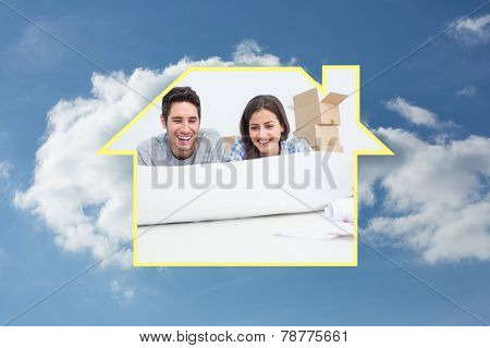 Couple lying on the floor and holding a house plan against cloudy sky
