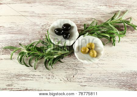 Two small plates with black and green olives and branches on painted wooden background