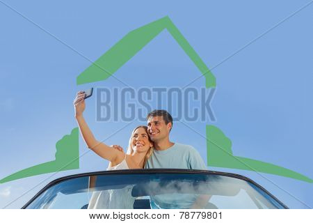 Cheerful couple standing in red cabriolet taking picture against house outline