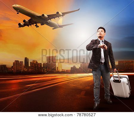 Young Man And Traveling Bag Luggage Standing On City Road Looking To Sky And Air Plane Flying To Air